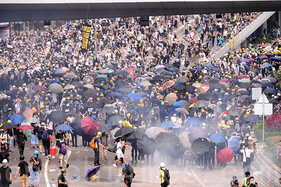 香港「反送中」示威衝突升高,警方12日下午在立法會旁對抗議民眾施放至少10枚催淚瓦斯和多次射擊橡膠彈,造成多人受傷。(宋碧龍/大紀元)
