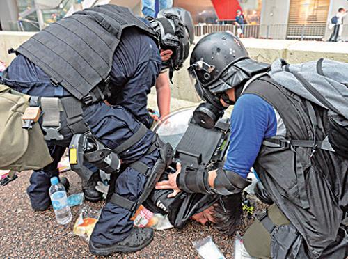 防暴警察將示威者按倒在地。(宋碧龍/大紀元)