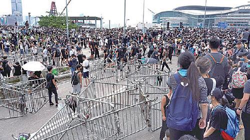 早上陸續有示威者聚集在龍和道,並以鐵馬和水馬做路障,堵塞龍和道,又佔據了夏愨道東西行6條行車線,要求撤回惡法。(李逸/大紀元)