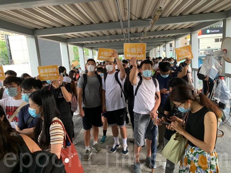近百名民眾聚集在中信大廈天橋上,部份人舉起寫有「撤回、香港加油」等的紙牌。(李逸/大紀元)