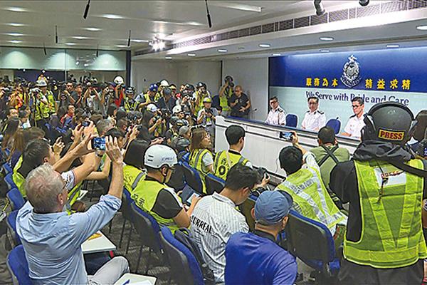 昨日採訪警方記者會的記者,響應記協呼籲穿上反光衣及頭盔,抗議警方暴力阻礙採訪。(AFP)