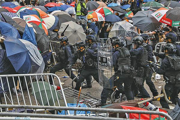 6月12日「反送中」集會,警方以警棍和催淚彈等暴力驅趕市民。(AFP)
