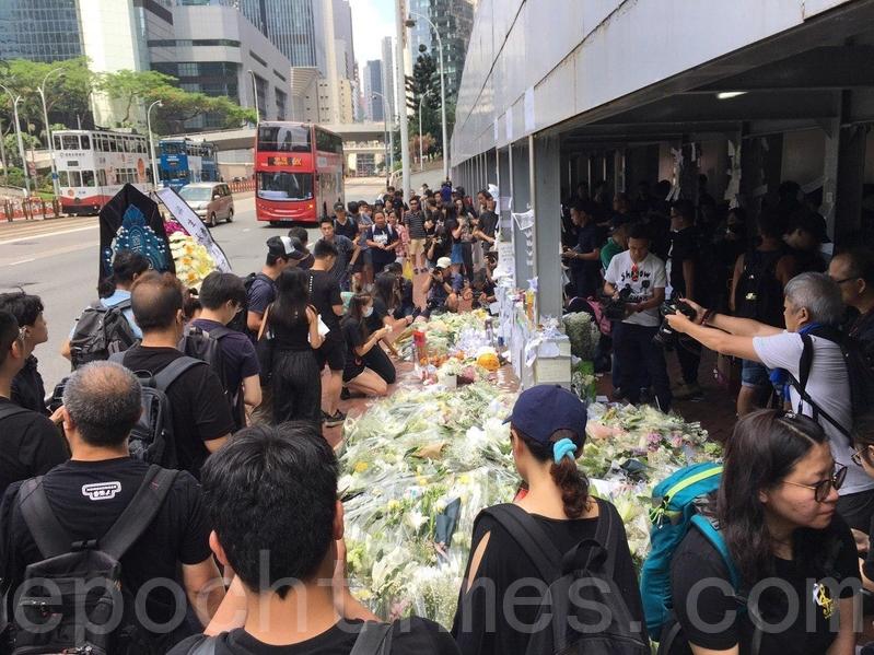 市民上午紛紛到太古廣場入口,將白色鮮花、悼念字條等獻給死者。(孫青天/大紀元)