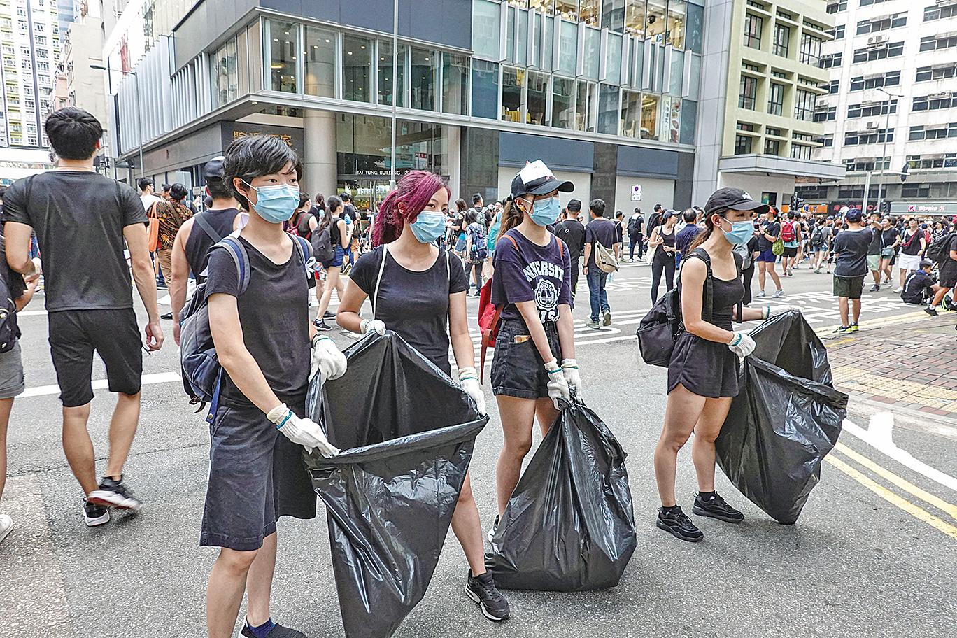 有不少年輕人自發在隊伍中回收垃圾。(余鋼/大紀元)