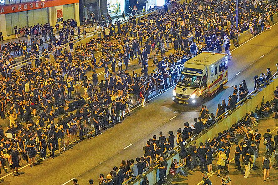 到達金鐘後,部份遊行人士佔領夏愨道,但在遇到緊急車輛通過時,均會自發讓路。(余鋼/大紀元)