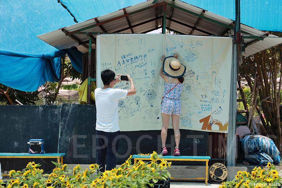 在藍色帳幕下,遊人可在留言板寫下自己的心聲。(陳仲明/大紀元)