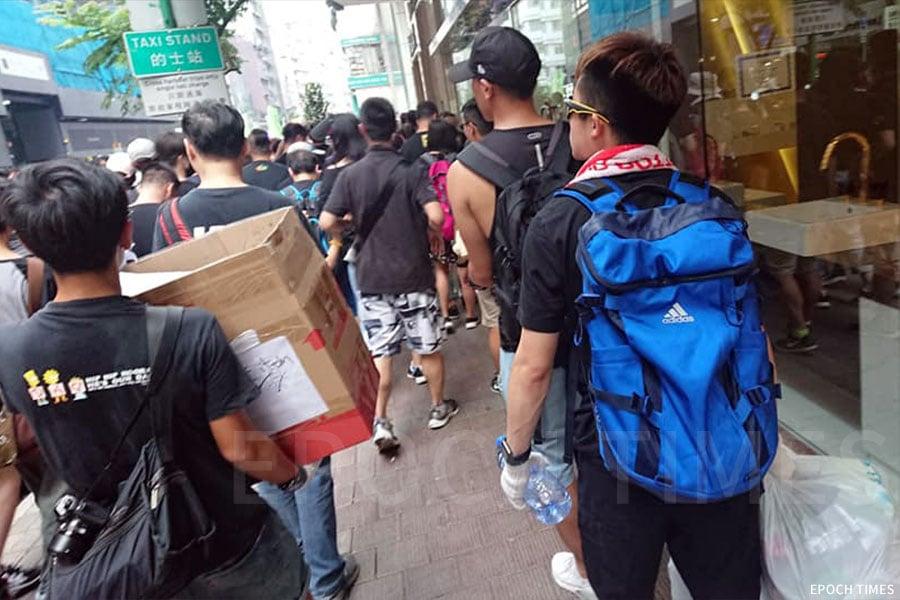 陳小姐及同行人士將收集到的塑膠垃圾,帶到遊行終點政總外的回收站。(受訪者提供)