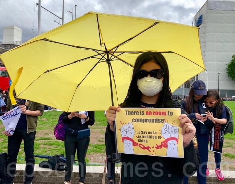 年僅13歲的 Marilyn 按主辦團體指引身穿黑色、撐起黃色雨傘及帶上口罩出席活動,以表示不滿。(唐詩韻/大紀元)