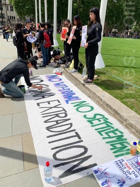 集會人士在地上寫大字標語。(唐詩韻/大紀元)