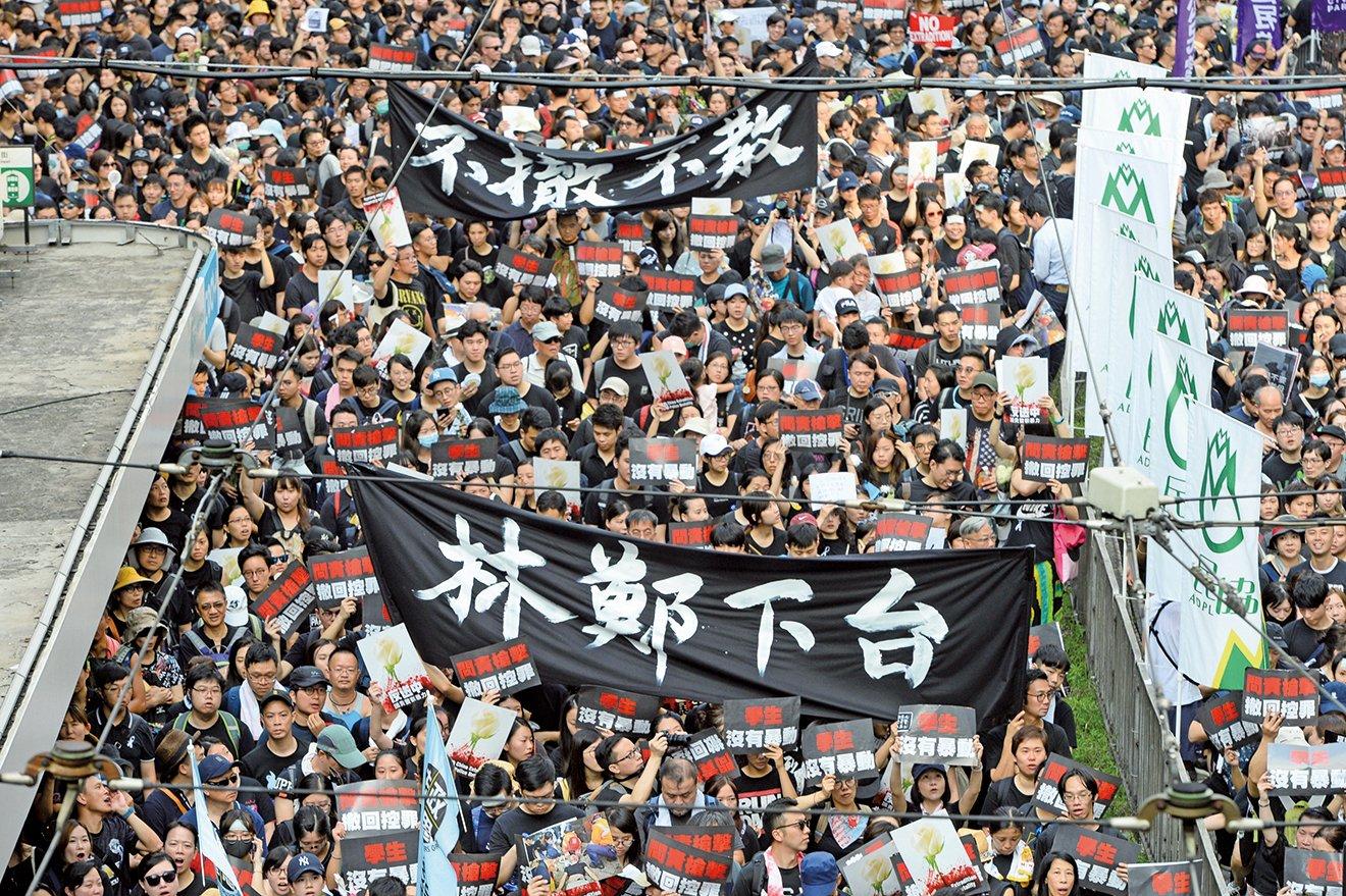在6月16 日「反送中」的遊行中,香港民眾高舉著「林鄭下台」「不撤不散」的橫幅。( 大紀元資料室)