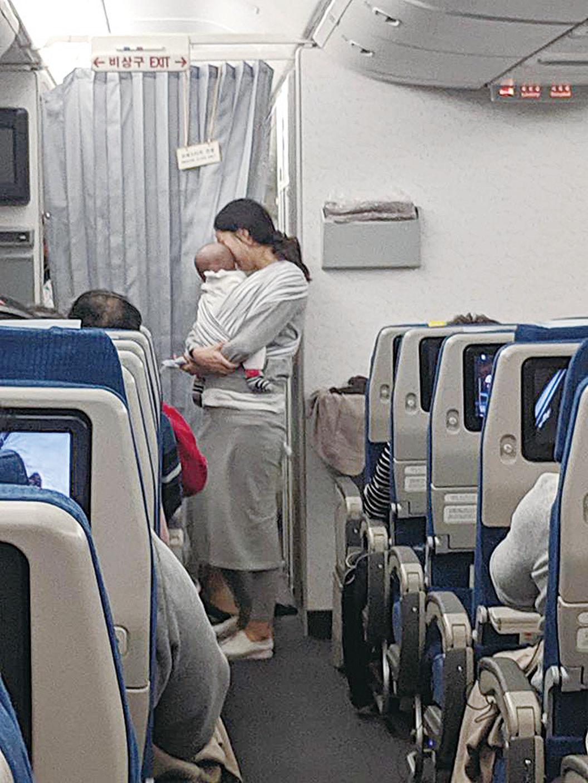 媽媽抱著4個月的小寶寶向乘客派發小禮物。(Dave Corona Facebook)