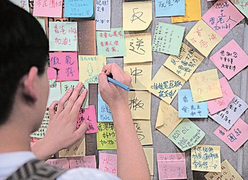 一名年輕人寫上心聲,貼在金鐘民主牆上。(Carl Court/Getty Images)