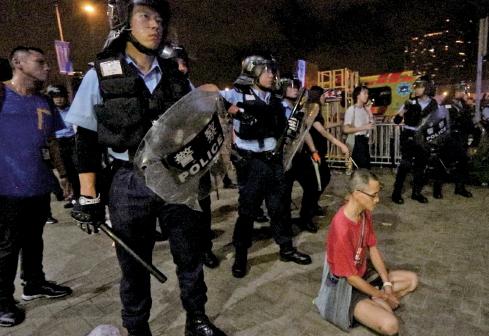 圖為6月9日,103萬人遊行後,立法會外仍聚集了大批市民。半夜警民衝突時,一名市民坐在防暴警察前。(蔡雯文/大紀元)