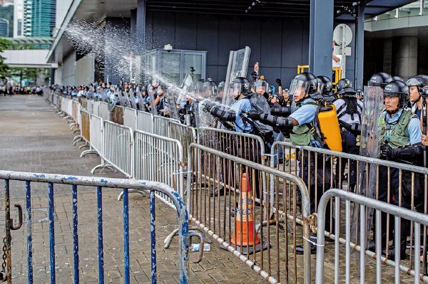 圖為6月12日立法會大樓外的防暴警察向集會市民噴射胡椒噴霧。(Getty Images)