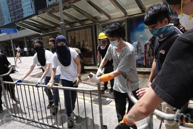 示威者並以鐵馬封隔稅務大樓對出的告士打道。(余鋼/大紀元)