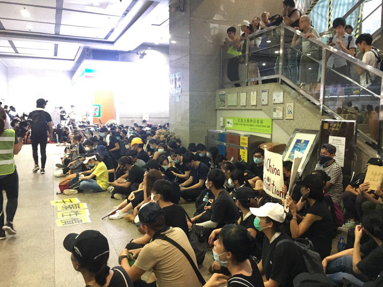 示威者進入旁邊的入境事務大樓後,並席地而坐,高呼「撤回」。(反送中已核實資訊頻道)
