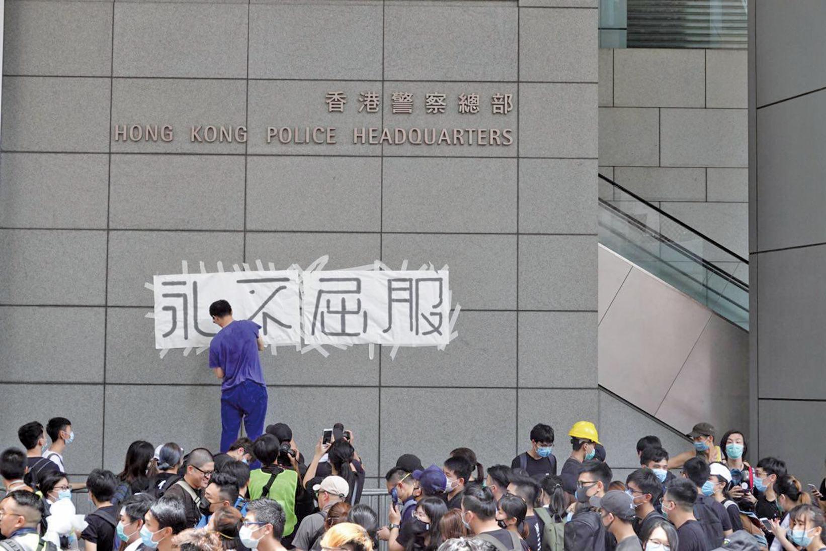 由於特首林鄭月娥未限時回應撤回修訂《逃犯條例》等四項民眾訴求,香港大專學界及網民從6月21日早上7時開始包圍香港政府總部。圖為示威者在香港警總牆上貼上「永不屈服」四個大字。(余鋼/大紀元)