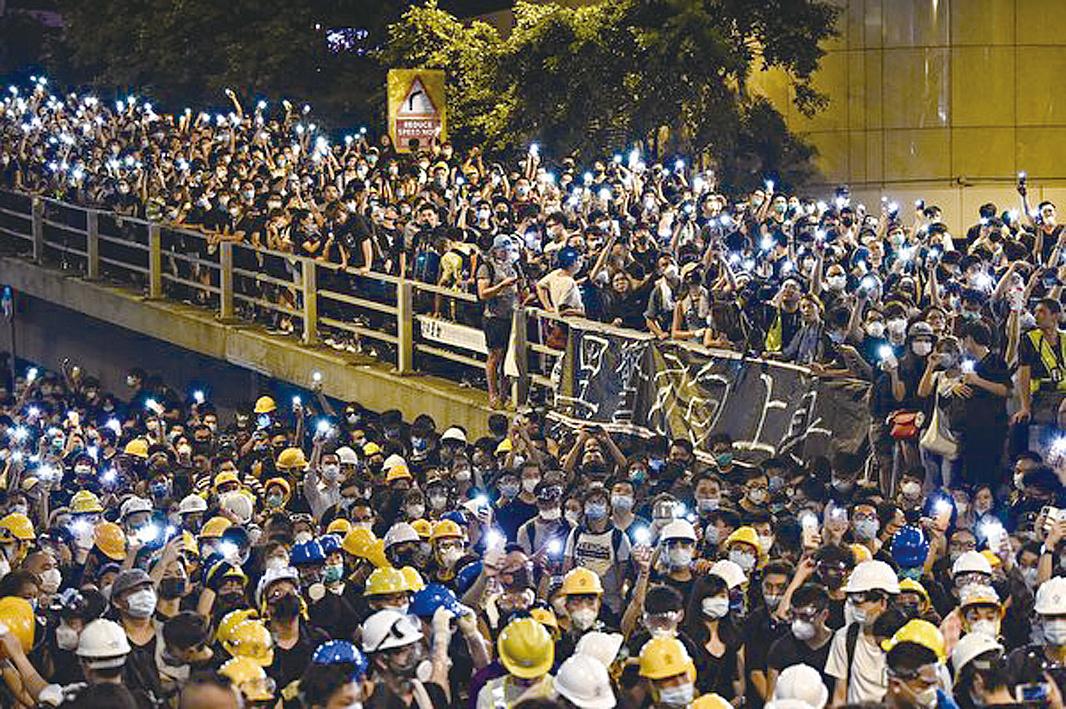 6月21日入夜後,警察總部外聚集的示威者持續增加。(HECTOR RETAMAL/AFP/Getty Images)