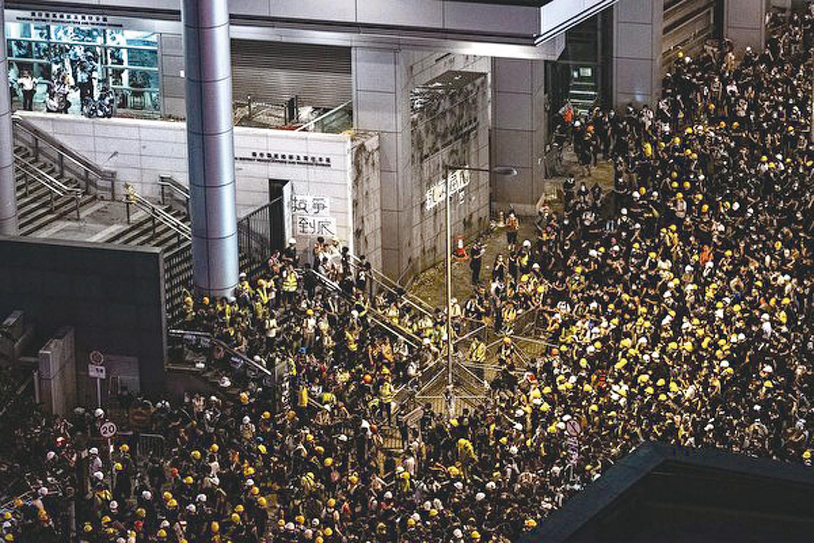 由於港府未回應學生4點訴求,大專學界宣佈,21日上午7時在金鐘海富橋,發起包圍政府總部、和平表達訴求的不合作運動。圖為入夜後,警察總部外聚集的大批示威者。(PHILIP FONG/AFP/Getty Images)