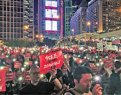 集會者亮起手機燈光,舉起撤惡法中英文標語。(胡宗翰/大紀元)