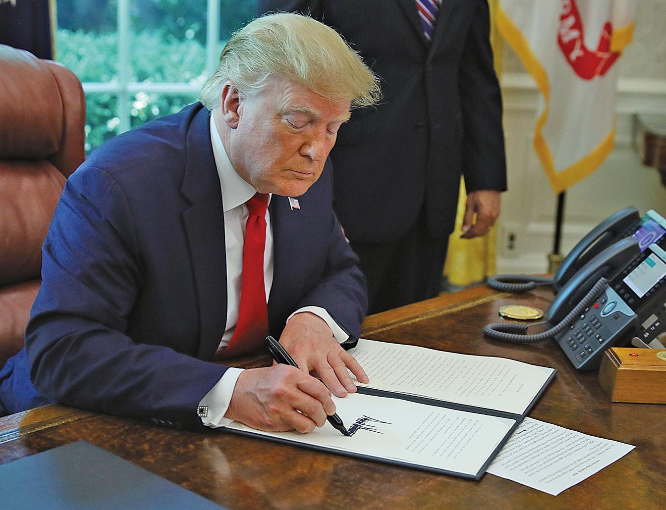 圖為2019年6月24日,特朗普簽署一項行政令來製裁伊朗最高領導人。(Getty Images)