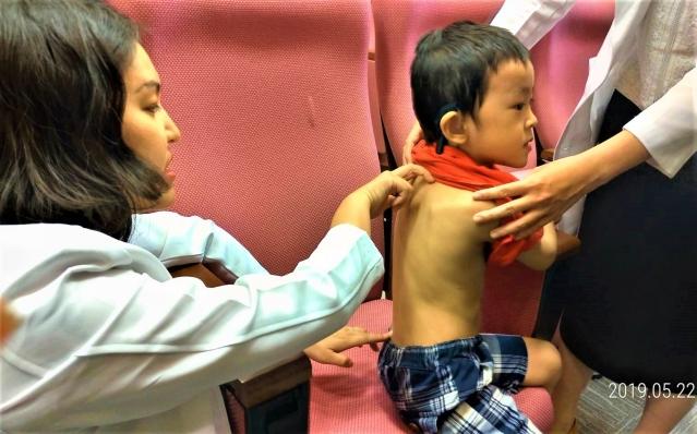 賴琬郁醫師示範,順著小兒脊樑骨兩側按壓或拉提,就可以增加抵抗力。(記者黃玉燕/攝影)