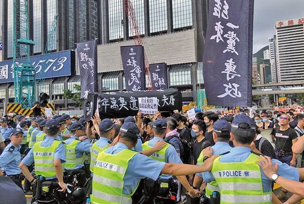 一批社民連成員抬著黑色棺材道具前往會展,遭警方築起人牆阻擋前進。前立法會議員梁國雄指,香港人已告訴世界,林鄭月娥不配做香港人的特首,共產黨也沒有兌現收回香港時的任何承諾。(李逸/大紀元)