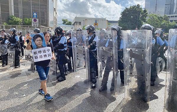 社運人士「女長毛」雷玉蓮手持抗議標語走過防暴警前。(李逸/大紀元)