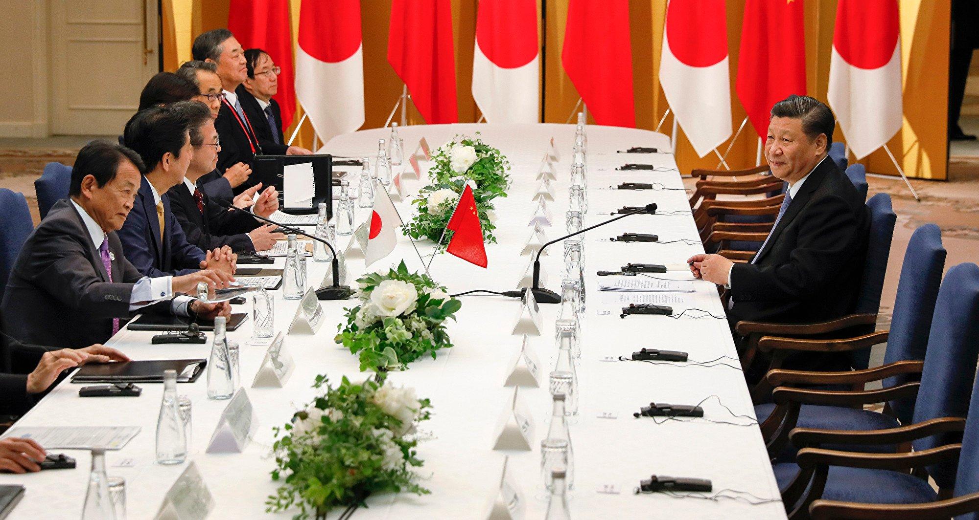 習近平與安倍晉三27日晚會面,「孤獨戰士」場面再現。 (Kimimasa MAYAMA / various sources / AFP)