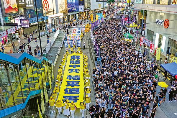 法輪功學員參與今年七一大遊行,隊伍中「解體中共 結束迫害」的巨型向天橫幅震撼人心。(大紀元資料圖片)