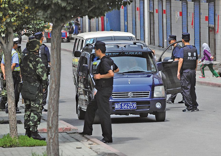 英國《衛報》報道說,中共警察在新疆海關秘密地把監視app安裝在遊客的手機上。圖為2009年7月17日,在新疆烏魯木齊街頭盤查的警察。(Getty Images)