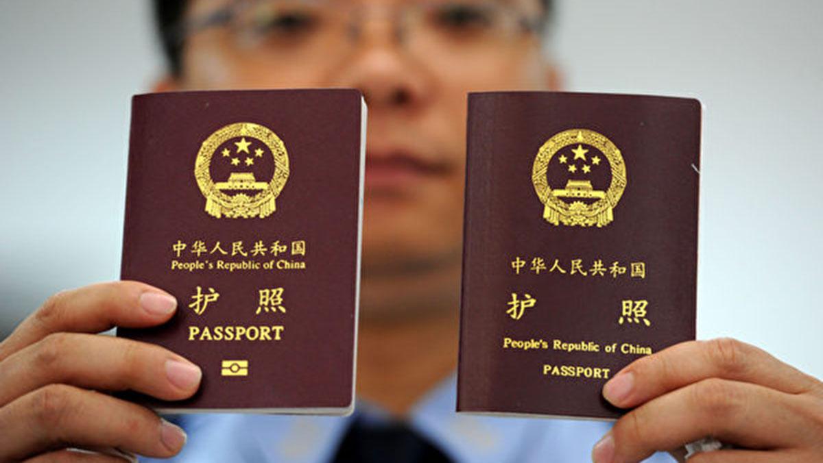 中國限製出國,強制收繳護照審查。圖為一名民警展示新版護照(左)和舊版護照。(大紀元)
