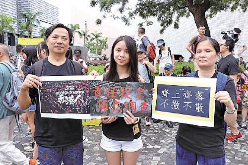 大學四年級生陳小姐(中)與父母一同上街反惡法。(蔡雯文/大紀元)