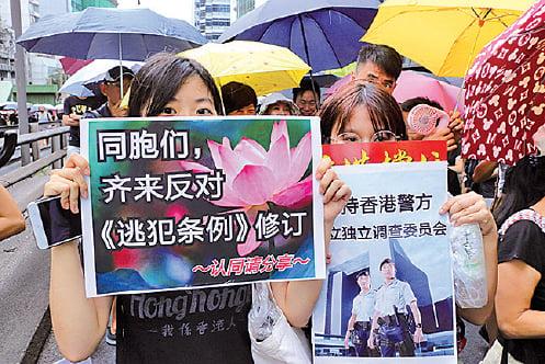 大學二年級學生童小姐和鄭小姐以簡體字標語呼籲大陸同胞齊反惡法。(蔡雯文/大紀元)