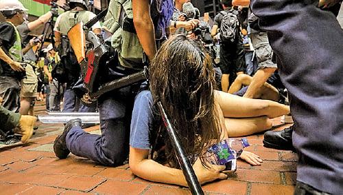 警方深夜11時前採取清場。圖為一女示威市民遭揹著長槍的警員壓倒地上。(Getty Images)
