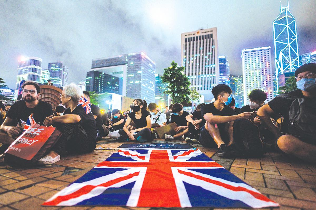 作為香港的前宗主國和《中英聯合聲明》的簽署方,英國在目前「反送中」運動中的角色關鍵且敏感。圖為「反送中」運動中抗議者展開英國國旗。(AFP)