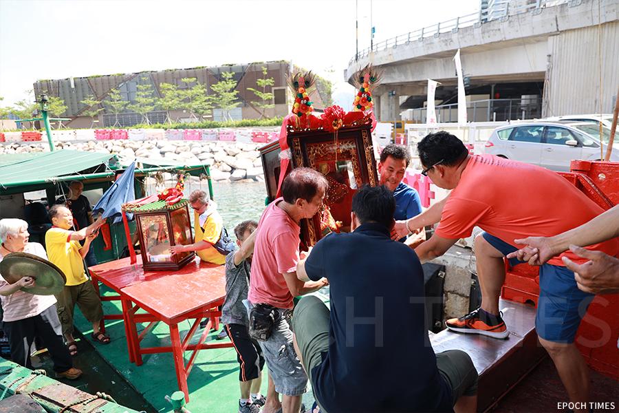 漁民在香港仔避風塘進行醮會,以淨化社區,圖為黃曆五月十八日的請神儀式,醮會負責人將天后請至接駁艇,送到主船上擺放供奉。(陳仲明/大紀元)