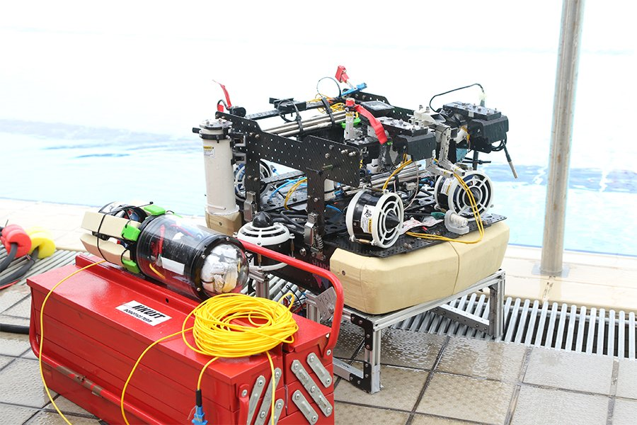 微型機械人(置在橙色工具箱上)以光纖連接及傳遞信號予水底機械人,在比賽中完成管道檢查項目。(受訪者提供)