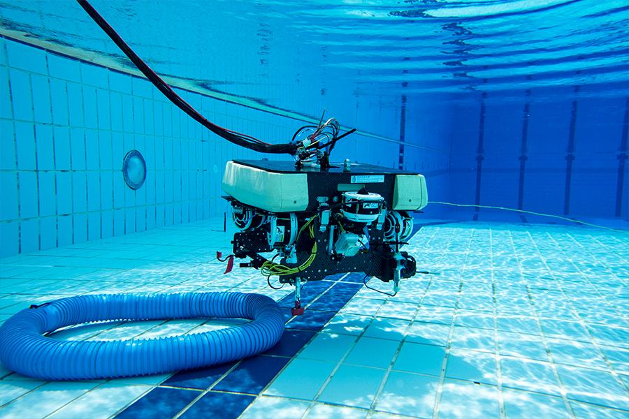 水底機械人在水底用機械臂拾起膠管。(受訪者提供)