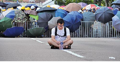 有市民坐在雙方防線中間,試圖阻止衝突發生。(龐大衛/大紀元)