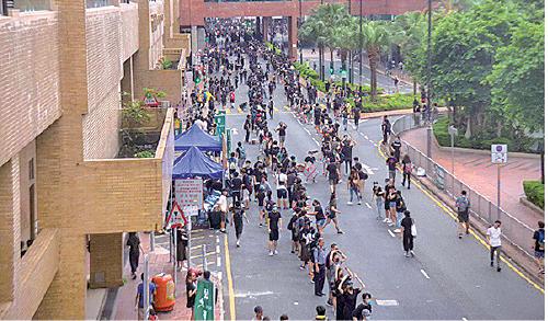遊行人士自發組成人鏈,向前方傳遞雨傘、頭盔等物資。(李逸/大紀元)