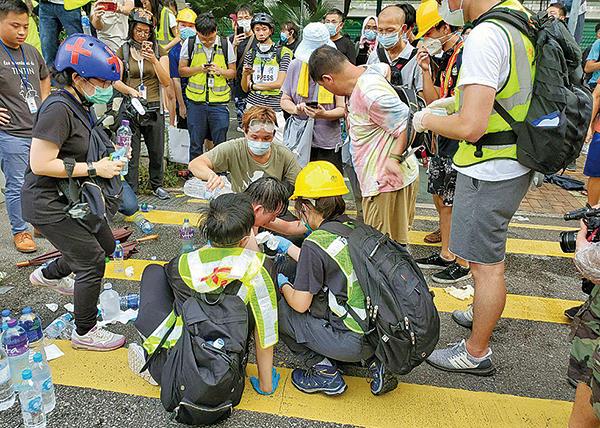遊行期間有記者被疑似是鐵通的雜物擊中倒地,按著肩膀,要由其他記者攙扶離開。(李逸/大紀元)