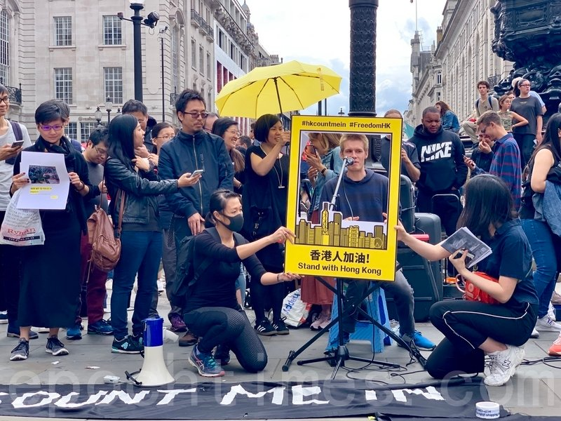 7月14日,德國籍街頭藝人David即興與港人合唱《Stand by me》,場面熱鬧引起熙來攘往的途人注意。(唐詩韻/大紀元)