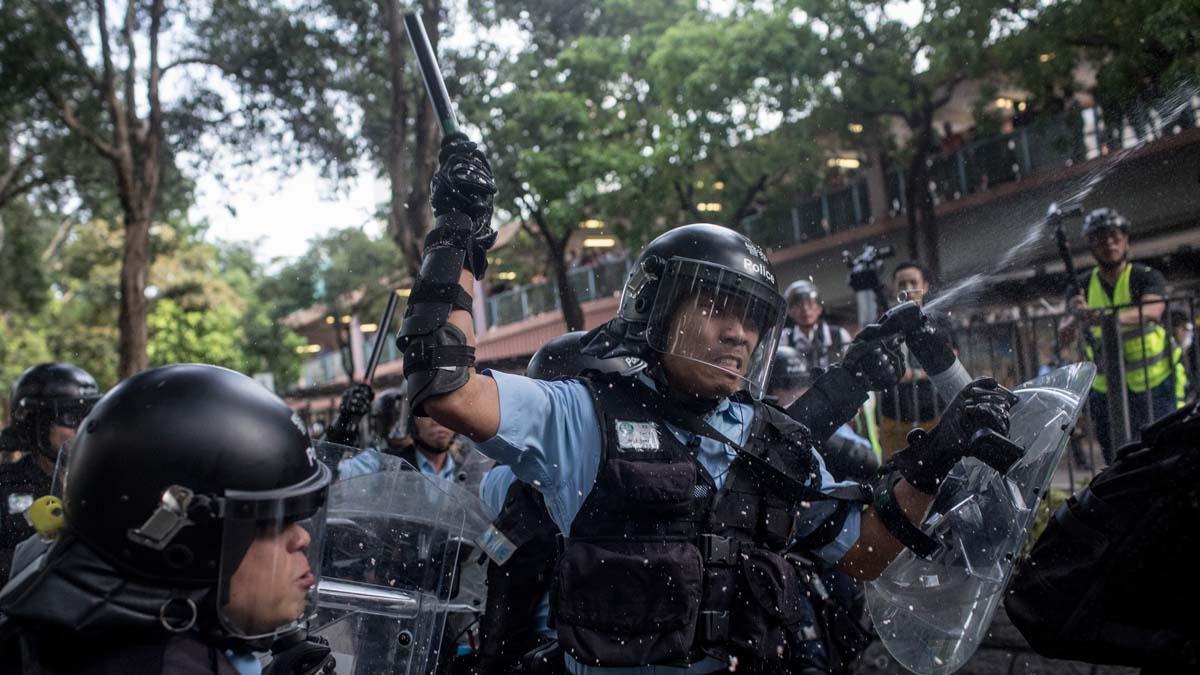 圖為周六的「光復上水」大遊行後,警察噴射胡椒噴霧,並手舞警棍衝向示威人群。(Chris McGrath/Getty Images)