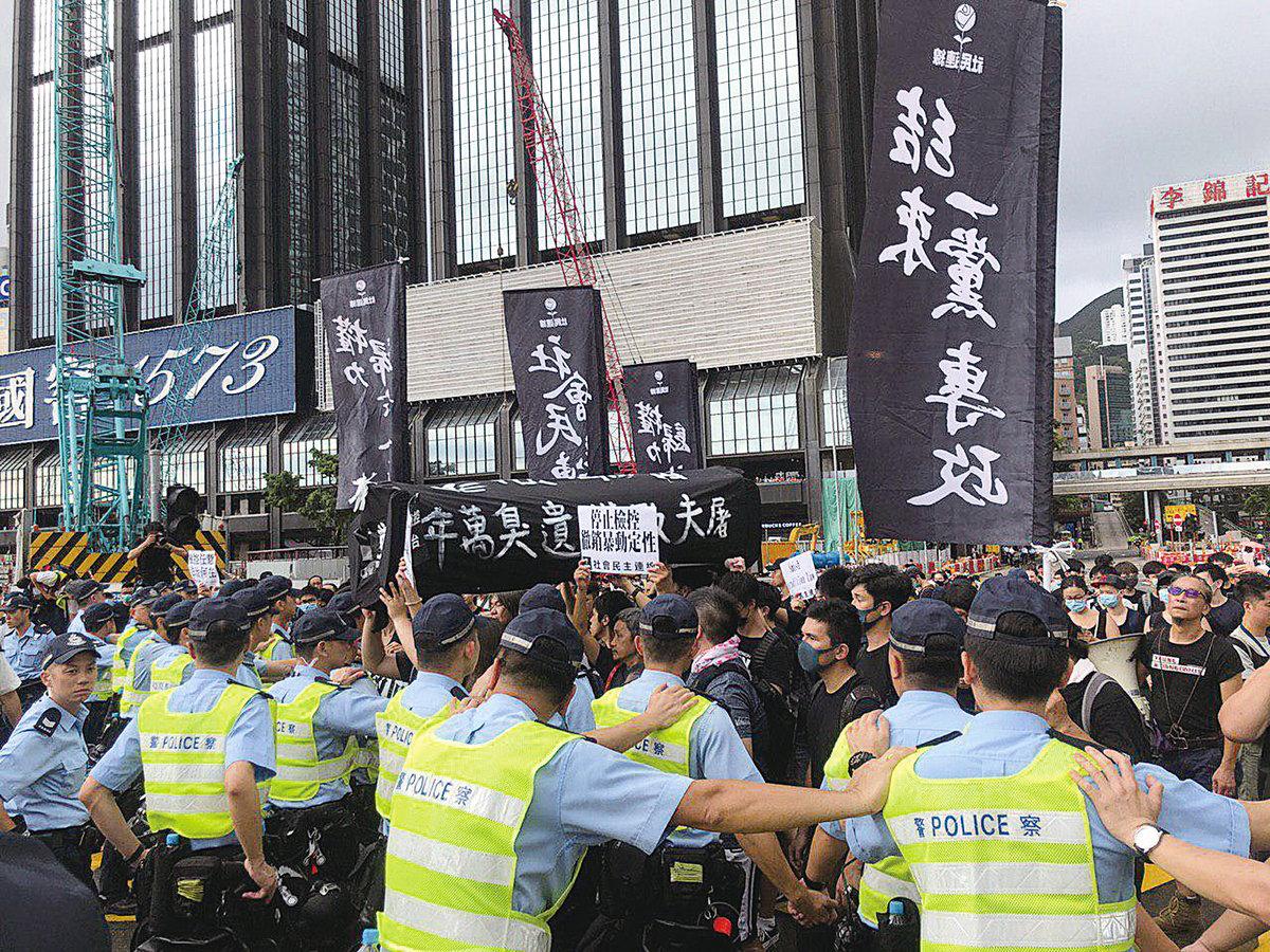 七一有社民連成員抬著黑色棺材道具前往會展,遭警方築起人牆阻擋前進。前立法會議員梁國雄指,香港人已告訴世界,林鄭月娥不配做香港人的特首,共產黨也沒有兌現收回香港時的任何承諾。(佘志誠/大紀元)