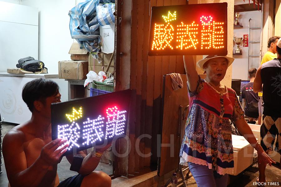 今年大澳龍舟精英賽結束後的夜晚,駿義龍體育會的會址前十分熱鬧,成員們今年首次在會址前擺酒席、唱歌,更舉起「駿義龍」的LED燈助陣。(陳仲明/大紀元)