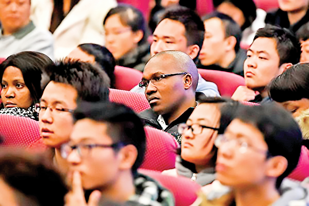 近日,山東大學「學伴」項目醜聞受到輿論廣泛關注。圖為2014年12月5日,南非留學生與中國大學生在北京清華大學聽取訪華的時任南非總統祖馬演講。(Getty Images)