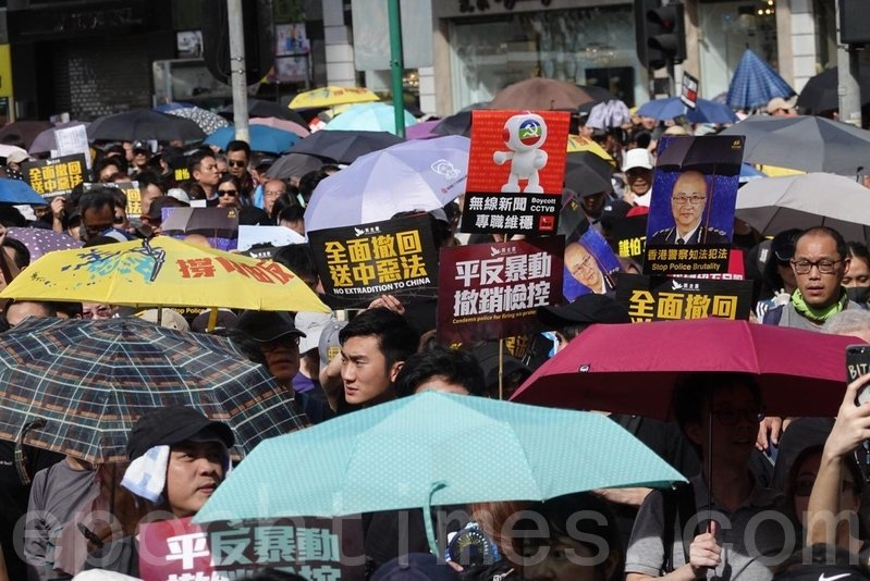 參加遊行的市民手持各種標語和海報。(余鋼/大紀元)