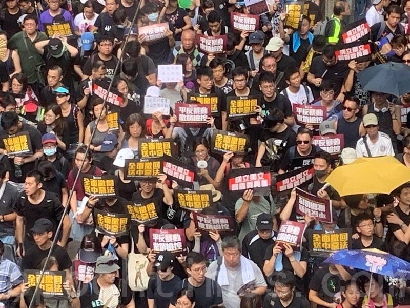 參加遊行的市民手持各種標語和海報。(駱亞/大紀元)
