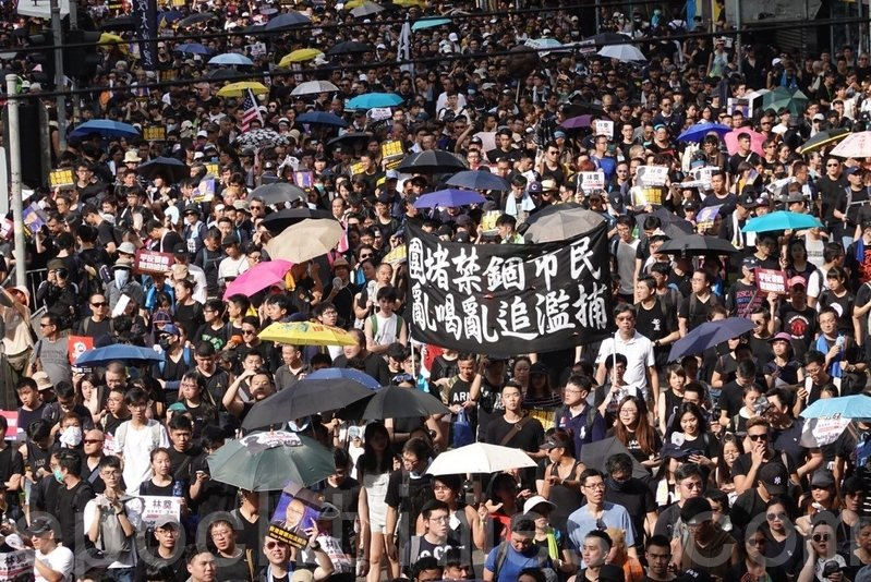 有市民舉起橫額抗議警方「圍堵禁錮市民 亂喝亂追濫捕」。(余鋼/大紀元)